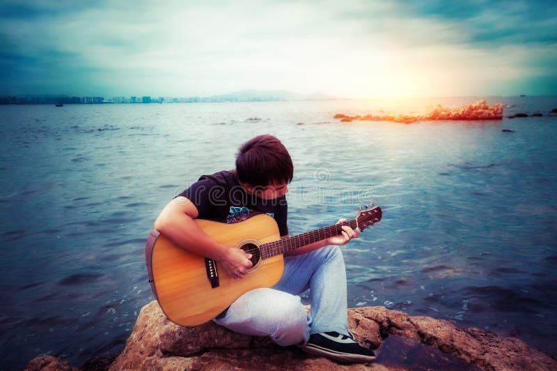 Jugar al muchacho clásico de la guitarra fotografía de archivo