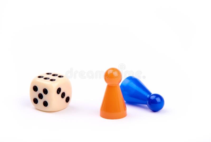 Jugar dados con los puntos negros y el número seis, dos pedazos del juego, la situación anaranjada como ganador y el azul que mie imagen de archivo