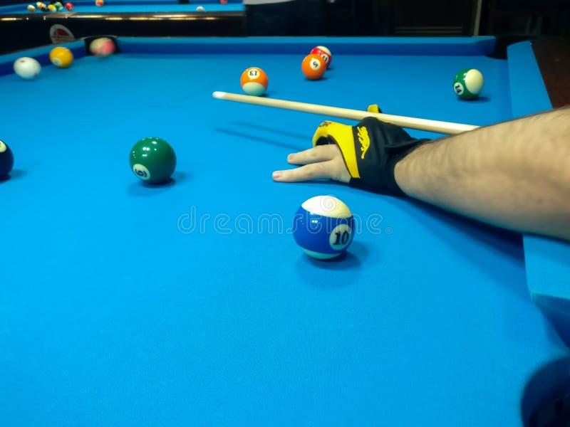 Jugar el billar, un tiro de un hombre que juega el billar en una mesa de billar azul foto de archivo
