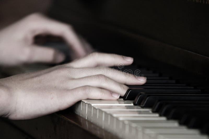 Jugar el funcionamiento de la música del piano con las manos imagen de archivo