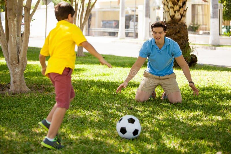 Jugar a fútbol con mi papá imagen de archivo libre de regalías