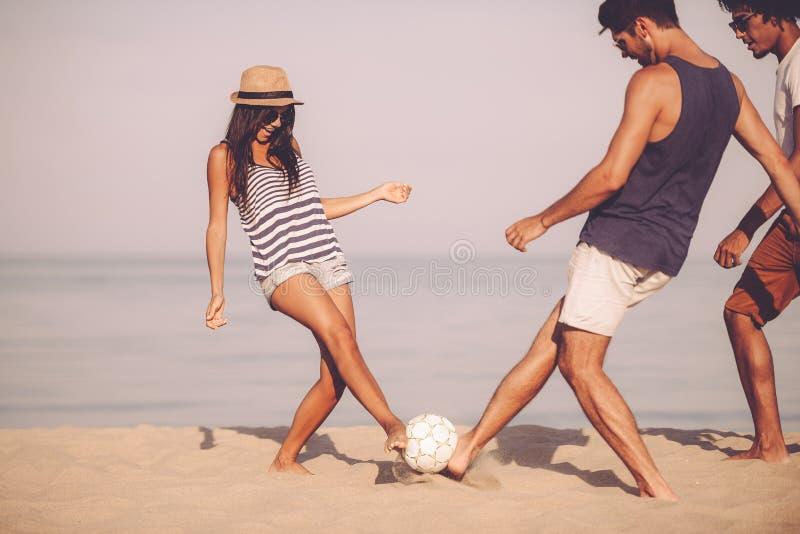Jugar a fútbol de la playa con los amigos imagen de archivo