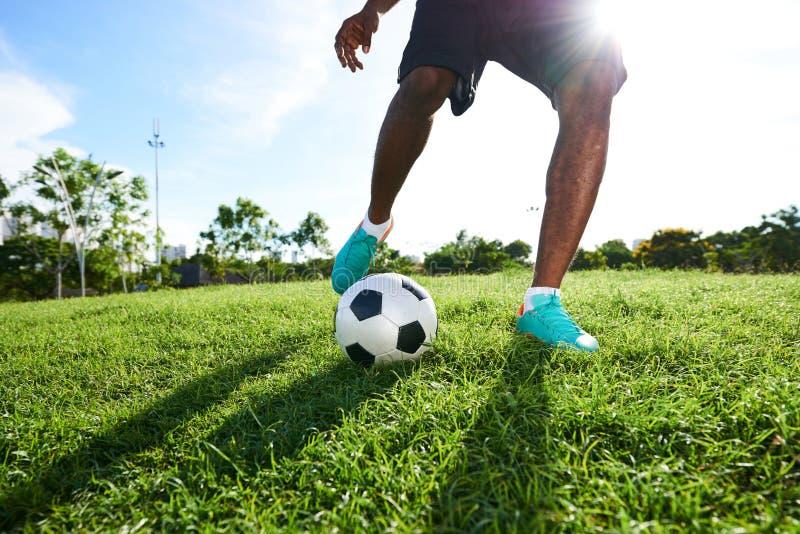 Jugar a fútbol en echada espaciosa imagenes de archivo