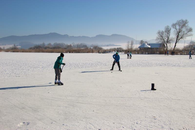 Jugar a hockey sobre hielo en un lago congelado Austria, Europa foto de archivo libre de regalías