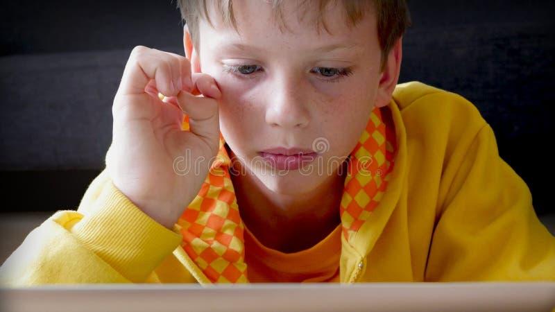 Jugar a juegos de la tableta, estudiante de la tableta foto de archivo