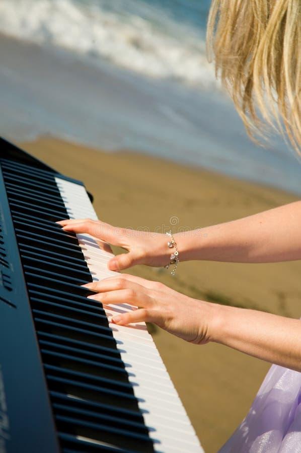 Jugar música en la costa imagen de archivo
