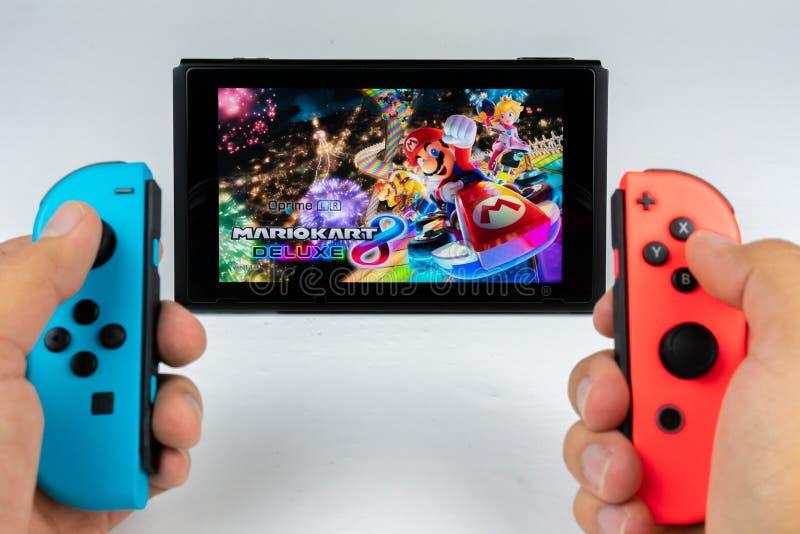 Jugar a Mario Kart Deluxe 8 en el interruptor de Nintendo imagen de archivo libre de regalías