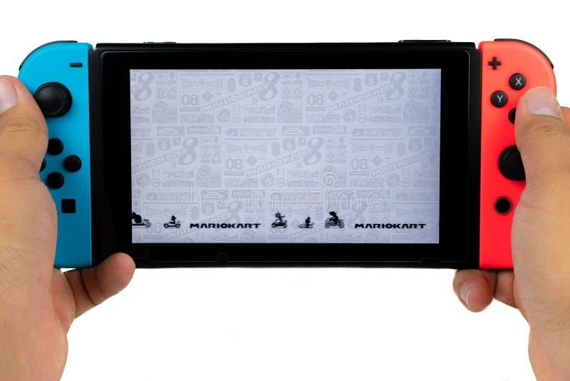 Jugar a Mario Kart Deluxe 8 en el interruptor de Nintendo fotos de archivo libres de regalías