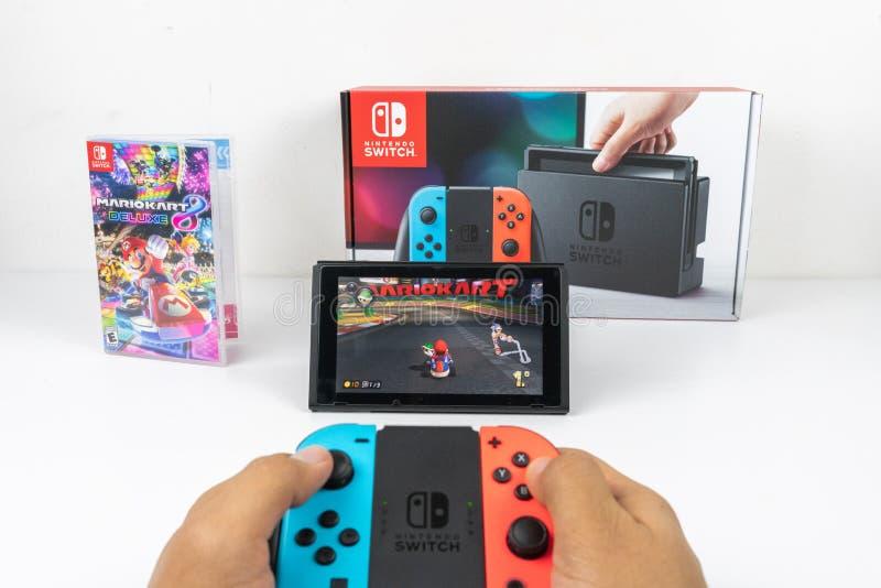 Jugar a Mario Kart Deluxe 8 en el interruptor de Nintendo imágenes de archivo libres de regalías