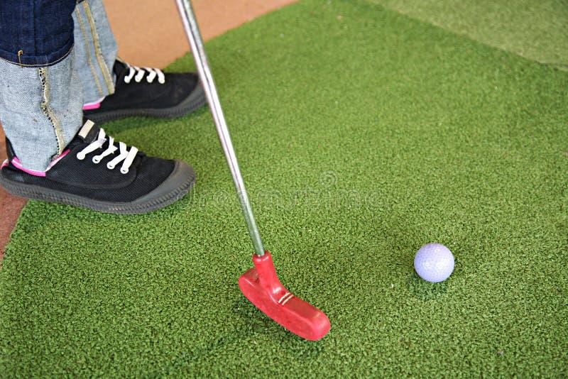 Jugar a mini golf con el putter rojo imagen de archivo