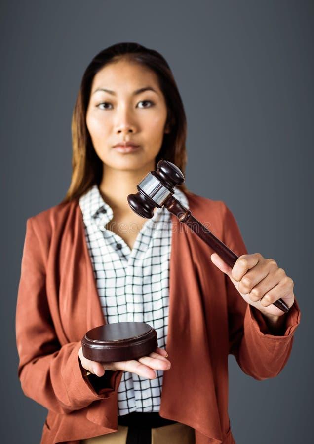 Juge féminin avec le marteau sur le fond gris images stock
