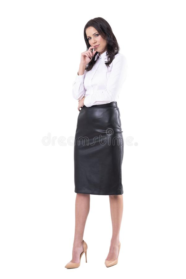 Jugeant la femme sceptique r?fl?chie d'affaires avec la main sur le menton regardant fixement la cam?ra soup?onneusement images stock