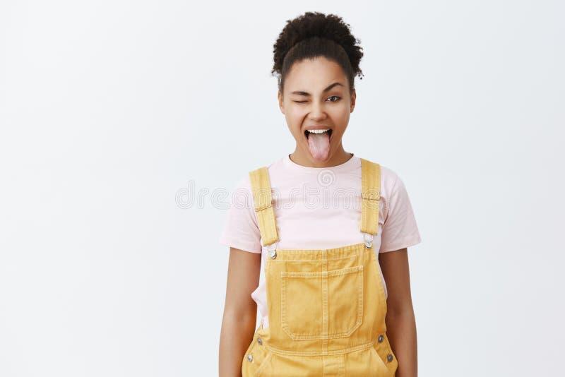 Jugend ist für Partei und Schauer Porträt des sorglosen glücklichen Afroamerikaners weiblich im gelben Overall über modischem T-S lizenzfreies stockbild