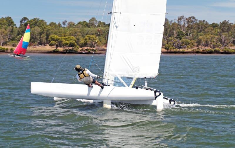 Jugend-Segeln kleines catamiran Boot mit einem weißen Segel auf einer Binnenwasserstraße lizenzfreie stockfotos