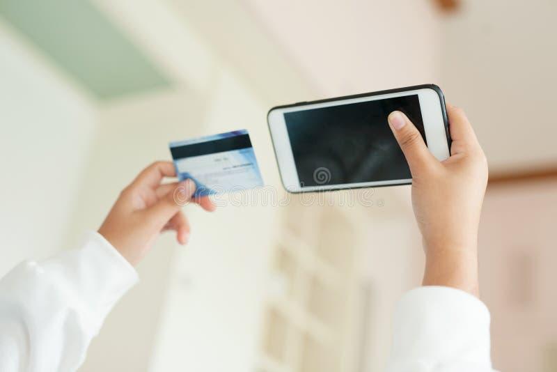 Jugend von der Frau, die intelligentes Telefon mit Kreditkarte beim auf Internet zu Hause kaufen hält stockbilder