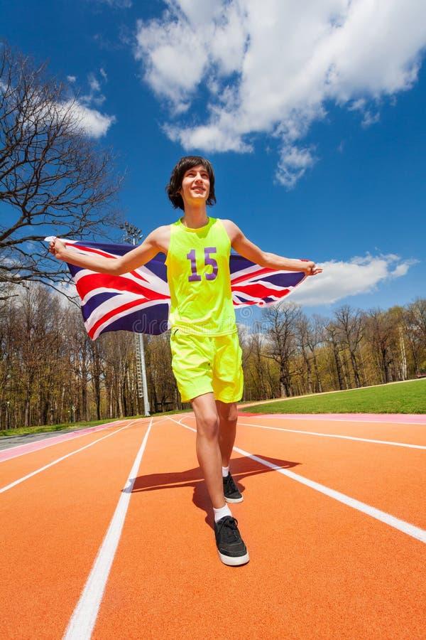 Jugendathlet, der mit Flagge von Großbritannien läuft lizenzfreie stockfotos