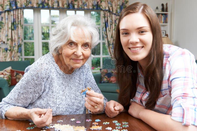 Jugendenkelin, die Puzzlen mit Großmutter tut stockbild