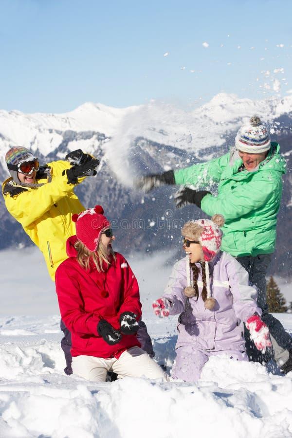 Jugendfamilie, die Schnee-Kampf in den Bergen hat stockbilder