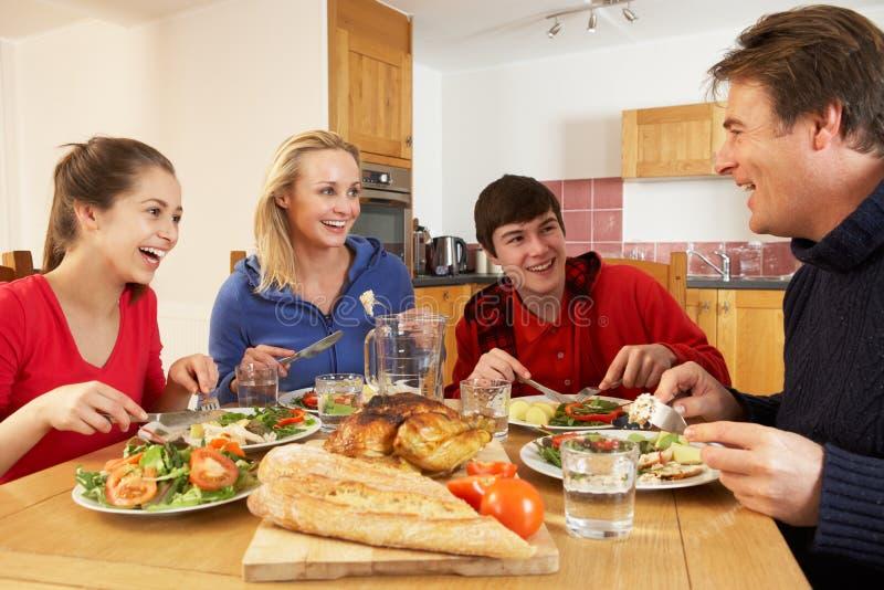 Jugendfamilie, die zusammen das Mittagessen in der Küche isst stockfotos