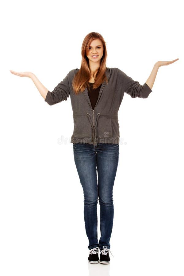 Jugendfrau, die etwas auf offenen Palmen darstellt lizenzfreies stockfoto