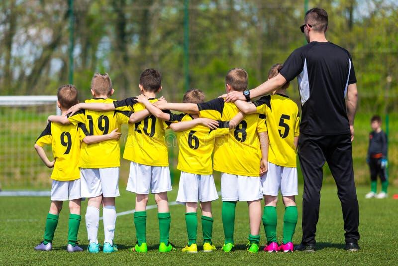 Jugendfußballteam mit Trainer Junges Fußballteam auf der Neigung lizenzfreie stockfotografie