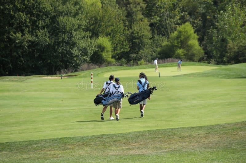 Jugendgolfspieler, die zu ihrem folgenden Loch im Golf gehen stockfotos