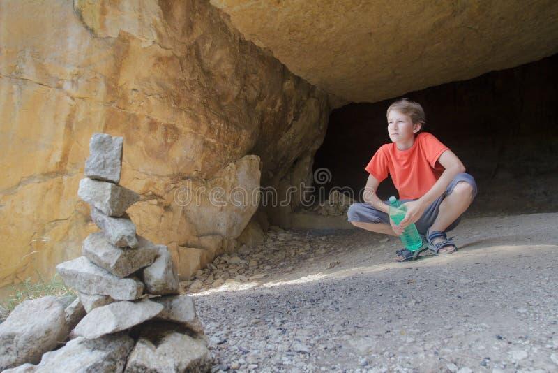 Jugendkind, das Bergblick von der Felsenhöhle mit Steinsteinhaufen auf Vordergrund betrachtet stockbilder