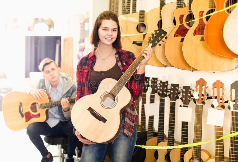 Jugendkunden, die auf passender Akustikgitarre in der Gitarre entscheiden stockfotografie