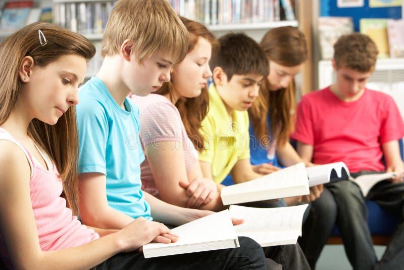 Jugendkursteilnehmer in den Bibliotheks-Lesebüchern lizenzfreie stockbilder