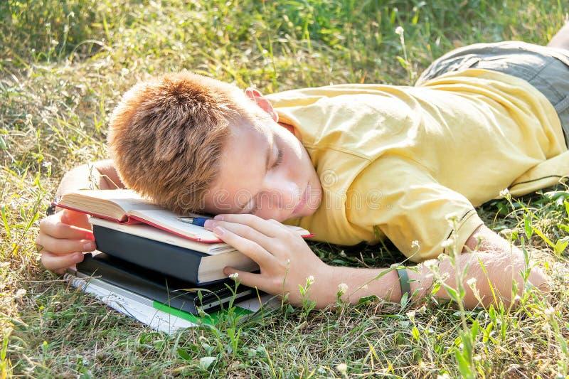 Jugendlügen und Schlafen auf dem Gras mit Buch lizenzfreie stockbilder