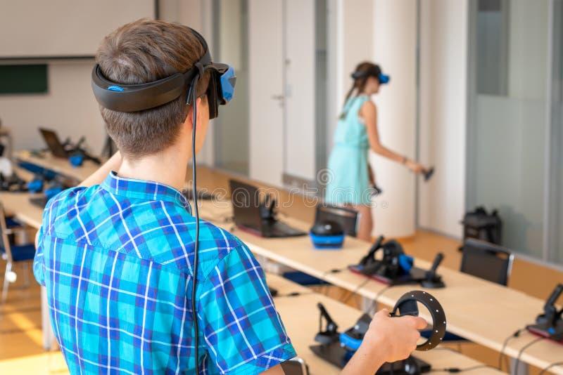 Jugendlich Altersjunge, der VR-Kopfhörer trägt, Prüfer in den Händen hält und neue Erfahrung im Videospiel genießt lizenzfreie stockfotografie
