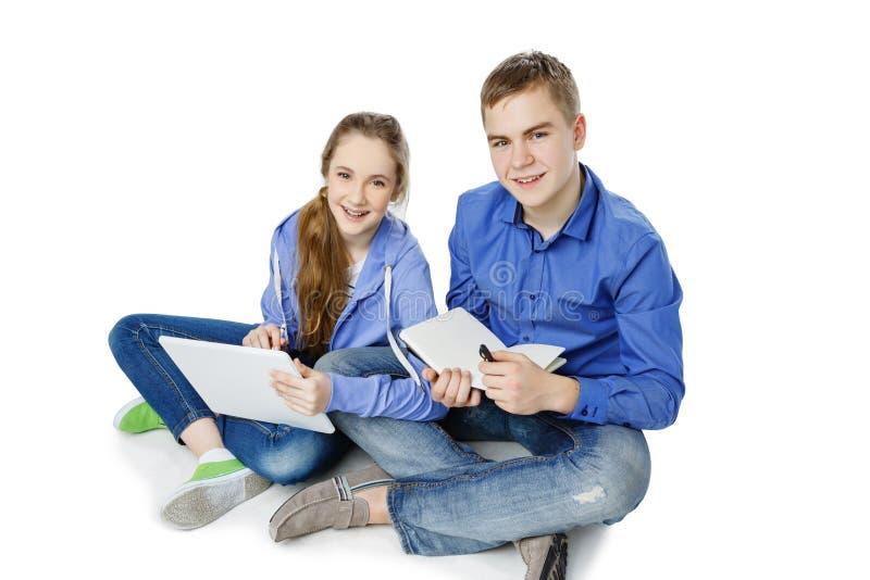 Jugendlich Altersjunge und -mädchen mit Tablette und Notizbuch stockfotos