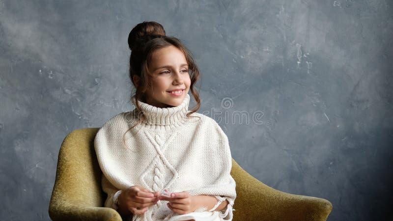 Jugendlich Altersmädchen, das auf dem altmodischen gelben Stuhl, Lächeln, die rechte Seite betrachtend sitzt lizenzfreie stockfotografie