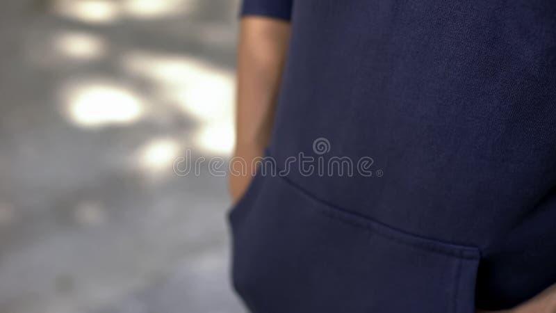 Jugendlich in der zufälligen Kleidung, die auf Verabredung, Hände in den Taschen, Erwartung wartet stockfotografie