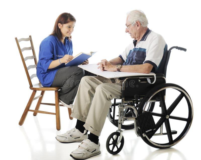 Jugendlich Freiwilliger liest zu den älteren Personen lizenzfreies stockfoto