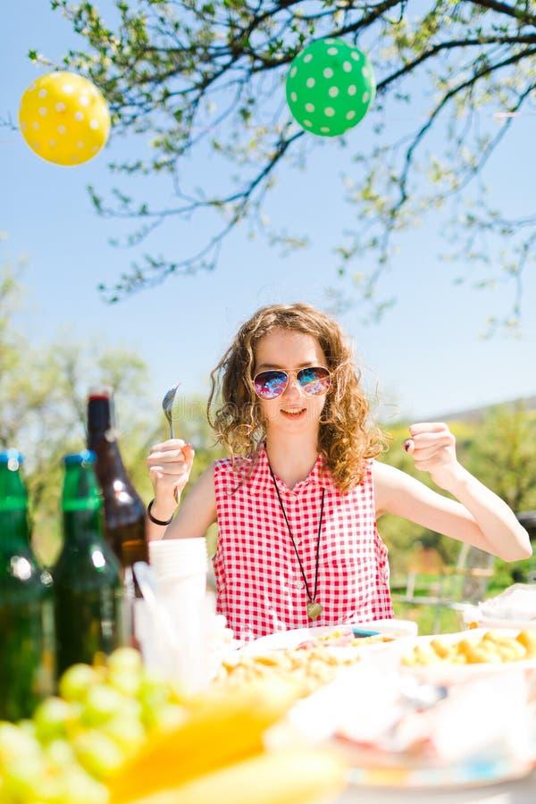 Jugendlich gealtertes M?dchen im roten karierten Hemd, das durch Tabelle auf Garten sitzt lizenzfreies stockbild