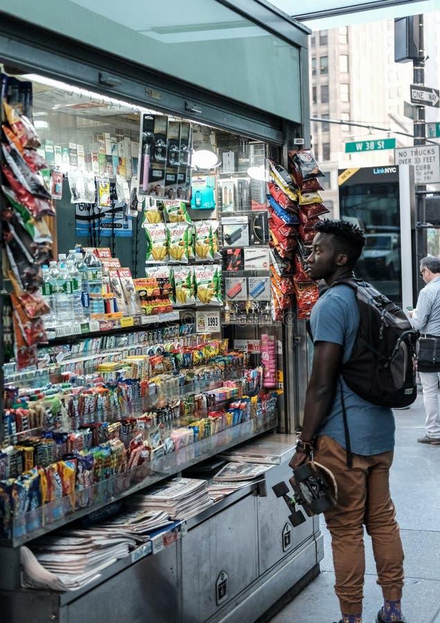 Jugendlich gesehen mit einem Skateboard auf einem New- Yorkzigaretten- und -süßigkeitenstand stockbild
