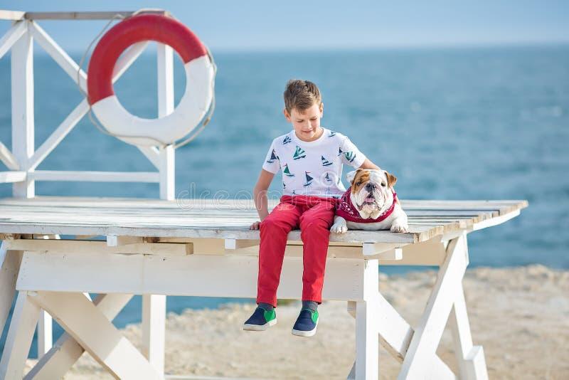 Jugendlich happyly Ausgabenzeit des hübschen Jungen zusammen mit seiner Freundbulldogge auf dem Seeseite Kinderhund, der zwei See lizenzfreies stockfoto