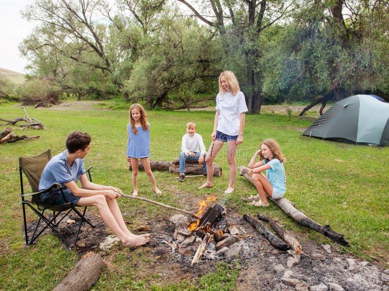 Jugendlich im Lager durch das Feuer lizenzfreies stockfoto