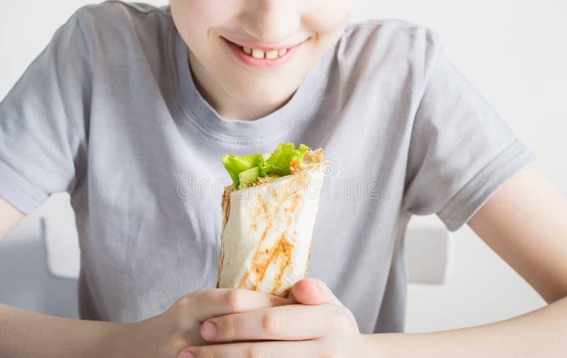 Jugendlich Junge, der Nahaufnahme shawarma der ungesunden Fertigkost isst Selektiver Fokus auf shawarma lizenzfreie stockfotos