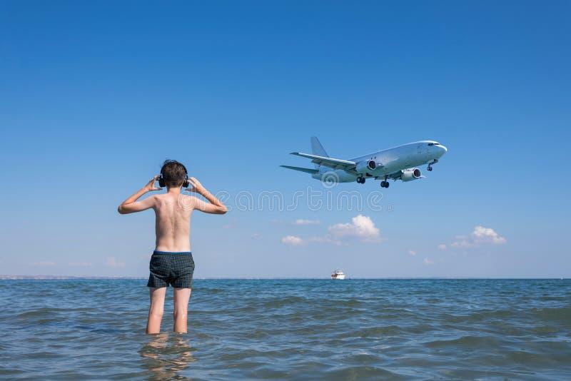 Jugendlich Junge in der Welle des Meeres auf dem Strand in den Kopfhörern unter den Landungsflächen Reisen auf ein Flugzeug mit K stockbild