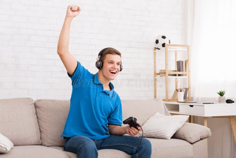 Jugendlich Junge, der zu Hause Sieg, Kopienraum feiert lizenzfreies stockfoto