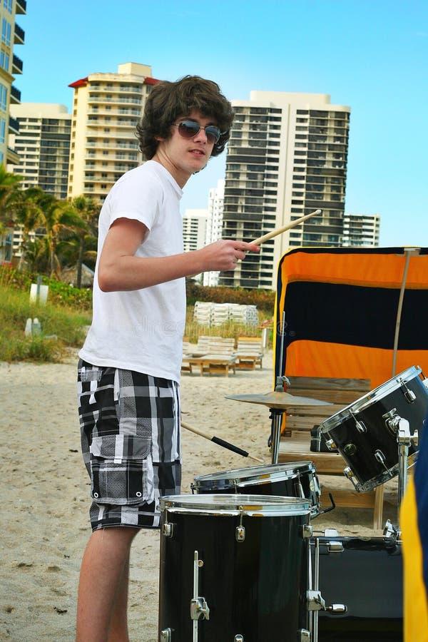 Jugendlich Junge mit Trommeln auf dem Strand lizenzfreie stockfotografie