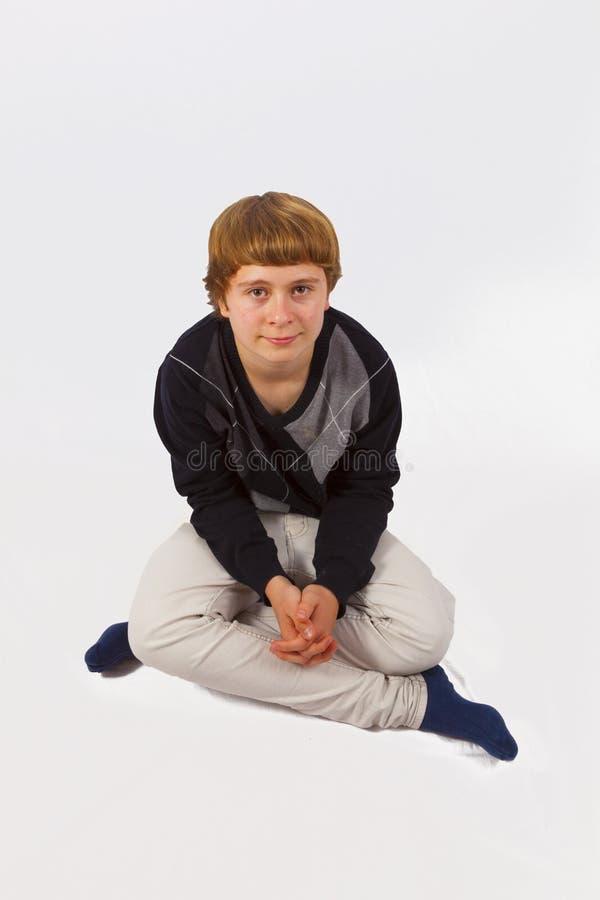 Jugendlich Junge sitzt im Schneidersitz aus den Grund lizenzfreies stockbild