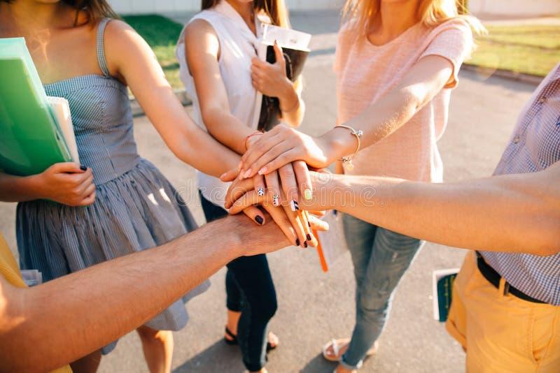 Jugendlich-Junge-Teamstudenten stapelten zusammen Hände stockbild