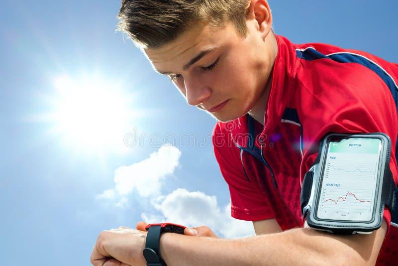 Jugendlich Läufer, der Einstellungen auf intelligenter Uhr überprüft lizenzfreie stockfotos