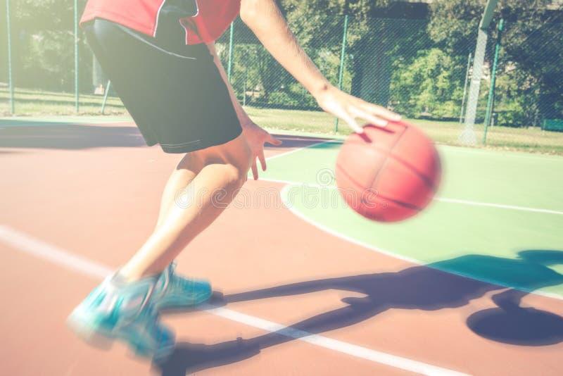 Jugendlich-Lebensstilkonzept des Jugendlichspielbasketballs gesundes sportliches im Freien im Frühjahr oder Sommerzeit lizenzfreie stockfotos