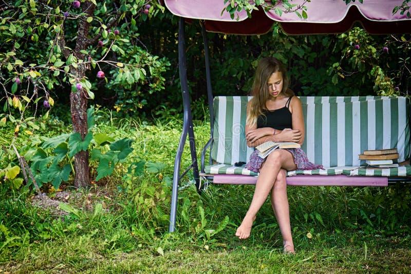 Jugendlich Mädchen liest ein Buch, das auf einem Gartenschwingen im Sommergarten sitzt stockbild