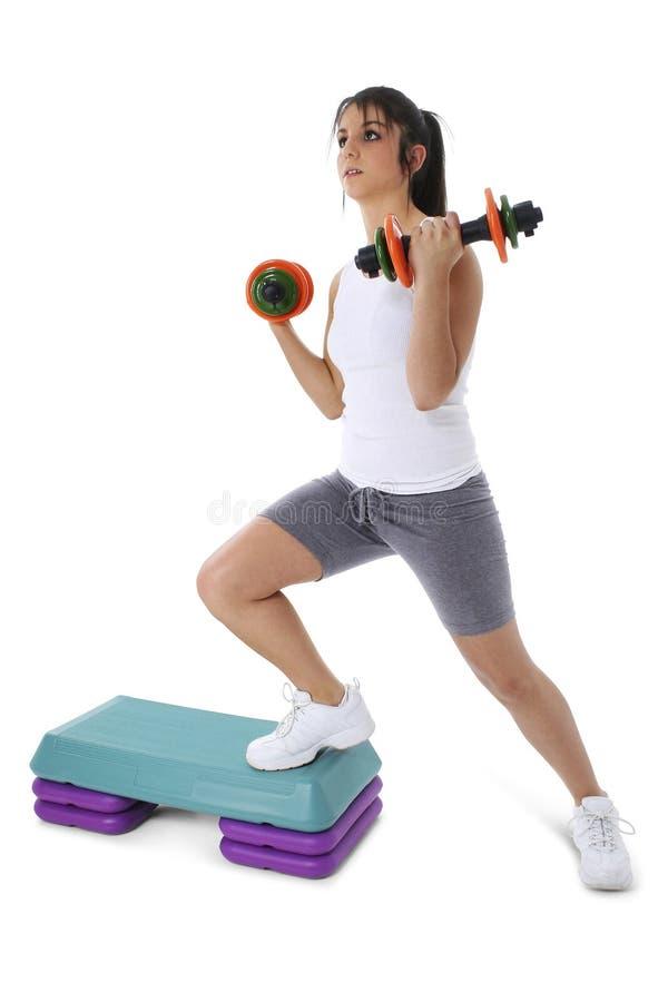 Jugendlich Mädchen auf aerobem Jobstepp mit Handgewichten lizenzfreies stockbild