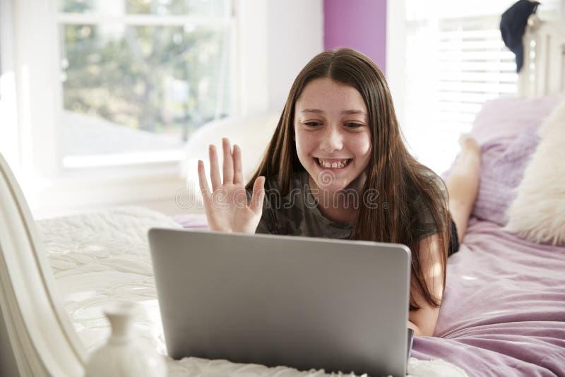 Jugendlich Mädchen, das auf dem Bett macht einen Videoanruf mit Laptop liegt stockbild